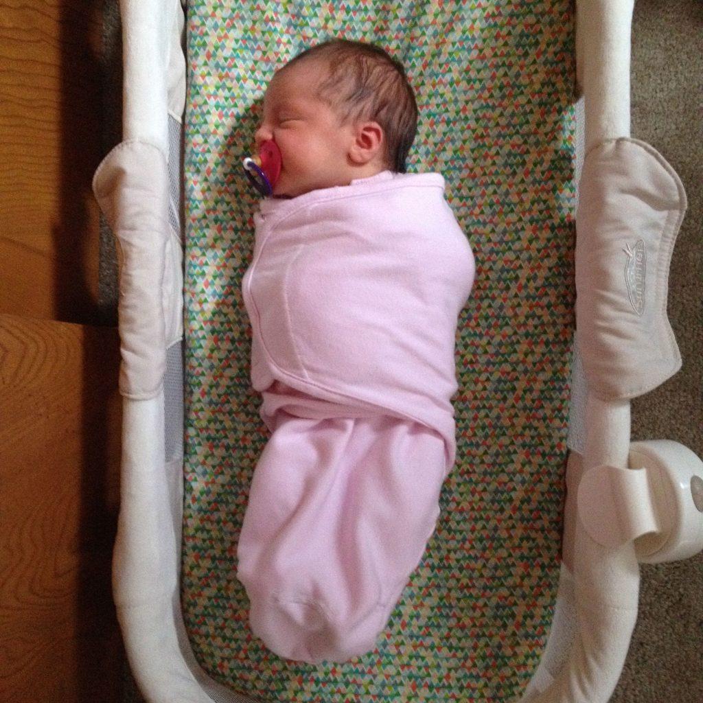 swaddled baby sleep in crib